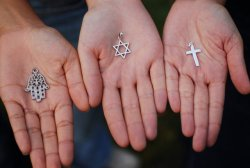"""Three outstretched hands hold symbols in their palms. On the left, is a hamsa, a palm-shaped amulet. In the center is a star of David, a six-pointed star. On the right is a cross, two perpendicular lines that look similar to a lower-case """"t""""."""