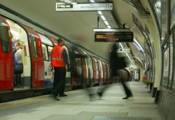 People walk on a subway platform, some leaving and some entering a red train with its doors open.