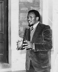 Smiling black South African man wearing a suit and gesturing with both of his hands in front of him.