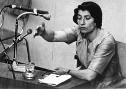 Zivia Lubetkin testifying behind a microphone in the courtroom at the Eichmann trial in 1961.