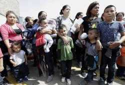 A group of women and children waiting to enter a bus station.