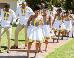 A procession of dancing men and women: men in tan pants and white long-sleeved shirts with a yellow/black pattern and women in white and yellow/black patterned dresses.