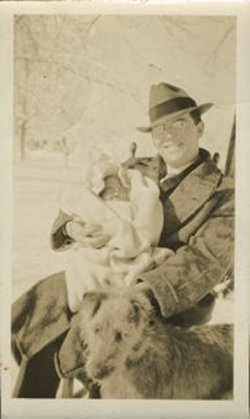 Waitstill Sharp sits while holding his daughter circa 1930. There is also a dog in the photo.