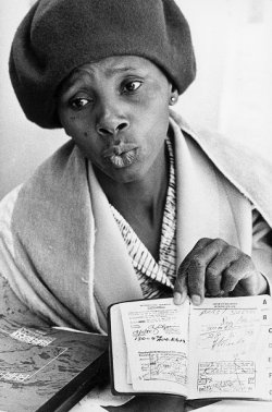 Black South African woman holds open passbook.
