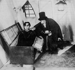 """Still image from the silent expressionist film """"The Cabinet of Dr. Caligari."""" In a small room with a small window, a man in a cloak and a top hat stoops over a man rising out of a large chest on the floor."""