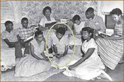 A group photo of the Little Rock Nine. Nine African American students sit in a living room together.