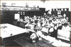 Students sit in rows of desks in an 1930s elementary school classroom.