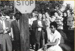 Young Elizabeth Eckford sits on a bench at a bus stop, surrounded by a crowd of white men.