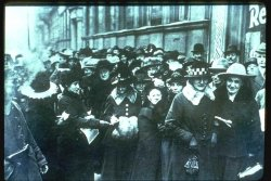A large crowd, consisting mostly of women, wait outside on the street to vote.