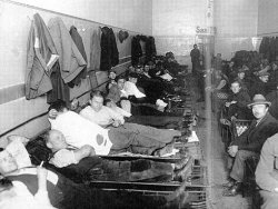 Men sit and lay down on rows of small cots in a long, thin room.