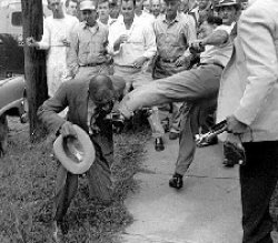 A man in a suit falls to his knee as another man kicks him in the torso. A crowd of men stand by, watching the violence.
