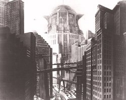 A black and white still from the futuristic 1926 film Metropolis directed by Fritz Lang. Includes futuristic-looking buildings with walkways going between them.