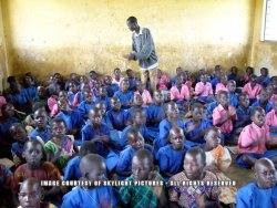 A large group of approximately 50 black African children sit on the floor, crammed into a bare room with tan walls. Some children are holding books. A teacher stands among the children.
