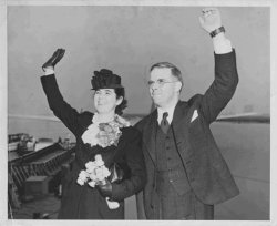 A man and a woman stand on the docks, waving goodbye. The woman is wearing a hat and carries a bouquet of flowers.