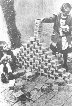 Two children around 10 years old, a boy and a girl, build a pyramid with stacks of inflated currency. The boy sits on the floor and looks up at the girl as she places more stacks on the pyramid. The pyramid looks to be approximately 2 feet high and 4 feet wide.