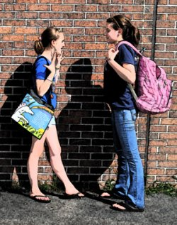 Two school-aged girls talk to each other while carrying schoolbags.