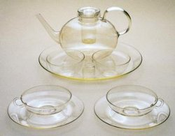 A set of clear glass tea service, including a teapot and two cups on a saucer.