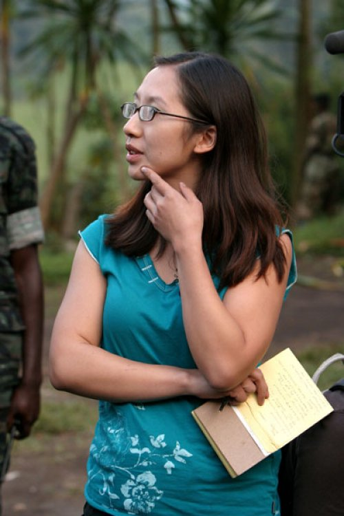 Leana Wen, a Chinese American woman, stands holding a notebook and pen. Palm trees are visible in the background, as well as the arm of a man who is out of the frame.