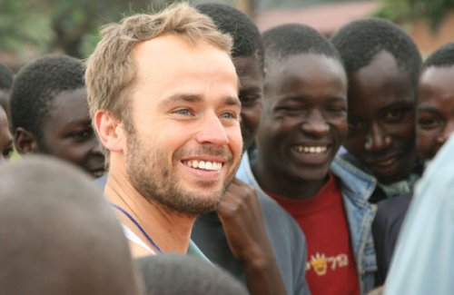 Will Okun, a white American, poses with a group of black Congolese young men.
