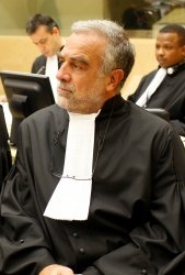 A photograph of a middle-aged Argentinian man with gray hair and a gray beard, wearing black judge's robes. Other people wearing judge's robes are visible in the background.