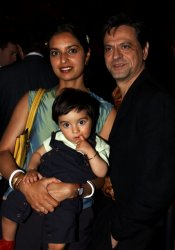 A woman and a man wear semi-formal clothing at an event. The woman carries a baby.