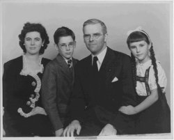 A family of four poses for a portrait. Pictured are Martha Sharp, Hastings Sharp, Waitstill Sharp, and Martha Content Sharp. The man and boy wear suits, while the woman and girl wear dresses. Taken approximately in the 1950s.